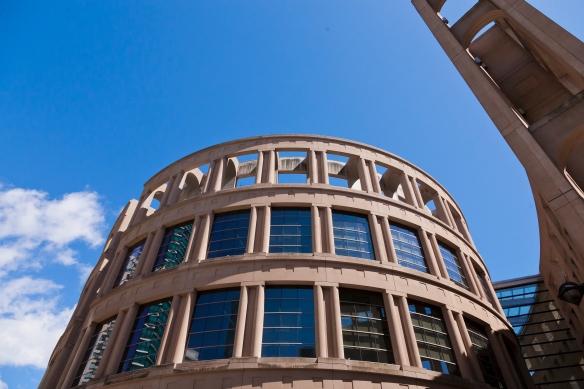 Photo couleur d'un immeuble rond ressemblant au Colisée de Rome, mais dont les fenêtres en verre aux deux étages supérieurs le placent fermement dans l'époque contemporaine.