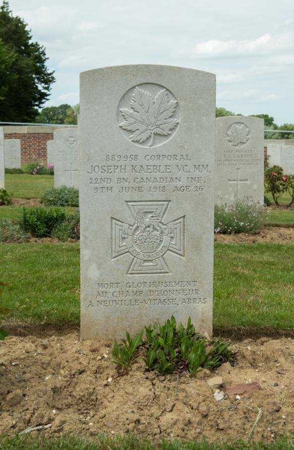 Photo couleur d'une pierre tombale devant laquelle quelques plantes commencent à pousser. On voit d'autres pierres tombales à l'arrière-plan.