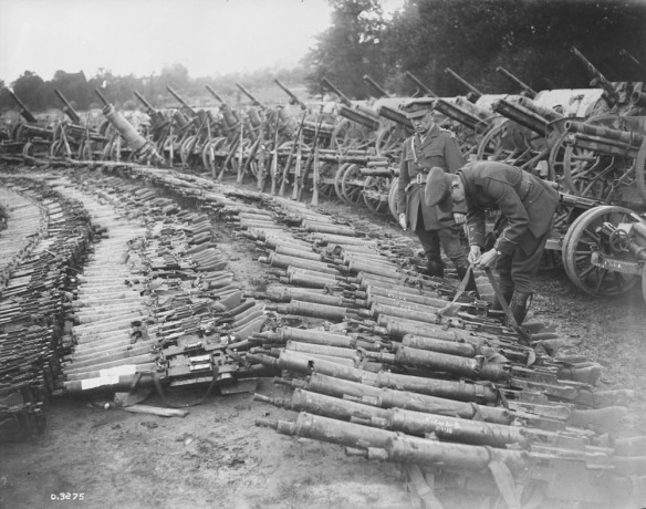 Photo noir et blanc de centaines de fusils et de mitrailleuses de diverses tailles reposant sur le sol. Un soldat, debout, regarde les armes tandis qu'un autre soldat se penche pour examiner la bandoulière d'un fusil.