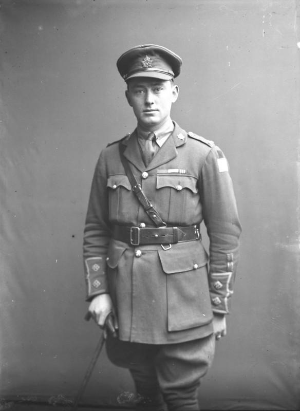 Photo noir et blanc d'un officier debout, tenant une canne.