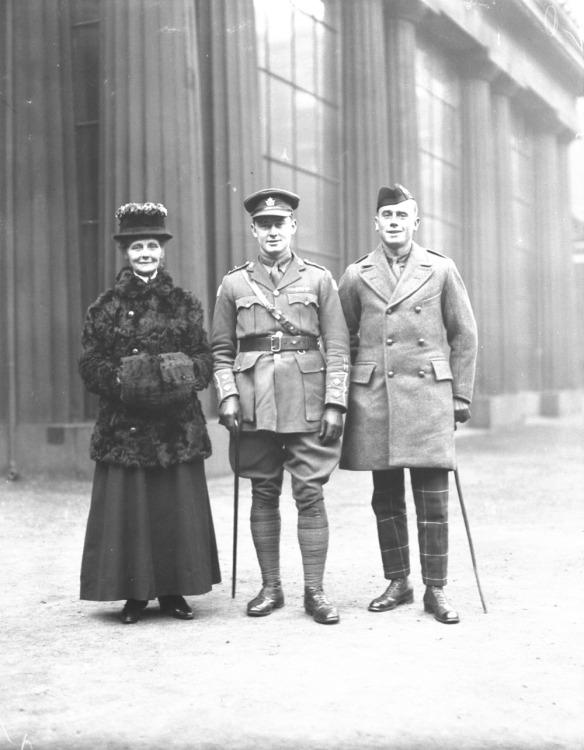 Photo noir et blanc de trois personnes debout, prenant la pose : une femme vêtue d'un manteau de fourrure, un officier avec une canne et un soldat avec une canne et un béret.