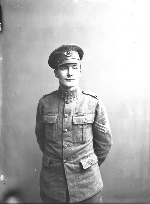 Photo noir et blanc d'un soldat en uniforme, debout, les mains derrière le dos.