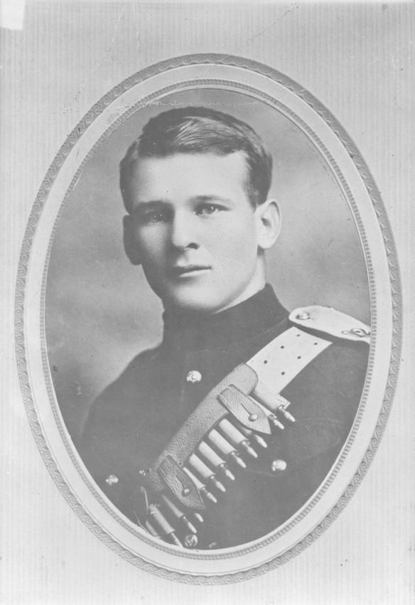 Photo noir et blanc du buste d'un soldat portant en bandoulière une ceinture pâle de sous-officier, des balles sur la poitrine.