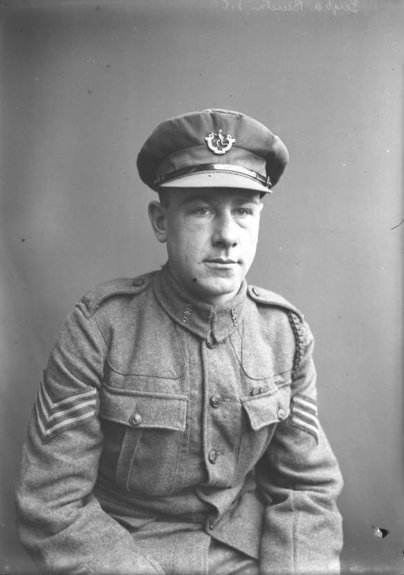 Photo noir et blanc d'un soldat assis, portant un uniforme et une casquette.