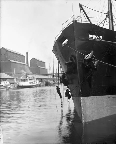 Photo noir et blanc d'un navire mis à quai. Quatre hommes travaillent, suspendus à des échelles accrochées à la proue.