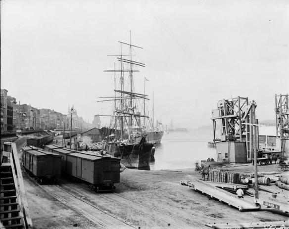 Une photographie en noir et blanc d'un chemin de fer longeant un quai où sont amarrés des bateaux.