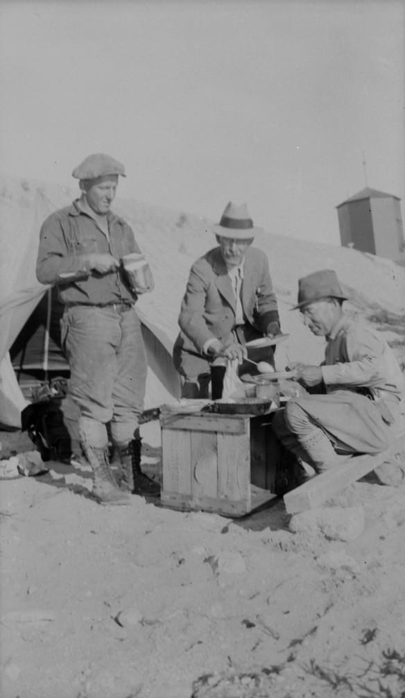 Photographie en noir et blanc de trois hommes entamant leur déjeuner à l'extérieur. Les hommes se tiennent autour d'une caisse en bois sur laquelle est posée la nourriture.