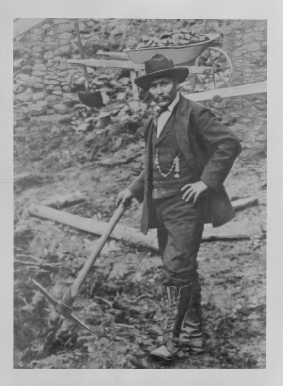 Photo noir et blanc d'un homme ayant une main placée sur la hanche tandis que l'autre tient une pioche de prospecteur. Il regarde droit vers l'appareil photo. Derrière lui se trouve une brouette remplie de pierraille.