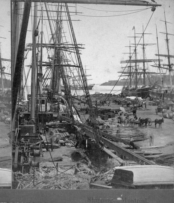 Photo noir et blanc de voiliers de marchandises mis à quai. Diverses marchandises sont entassées sur le quai et transportées ailleurs dans des charrettes tirées par des chevaux.