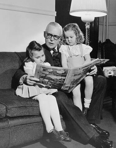 Photo noir et blanc montrant Louis St-Laurent assis sur un canapé, lisant un journal à deux fillettes assises de chaque côté de lui.
