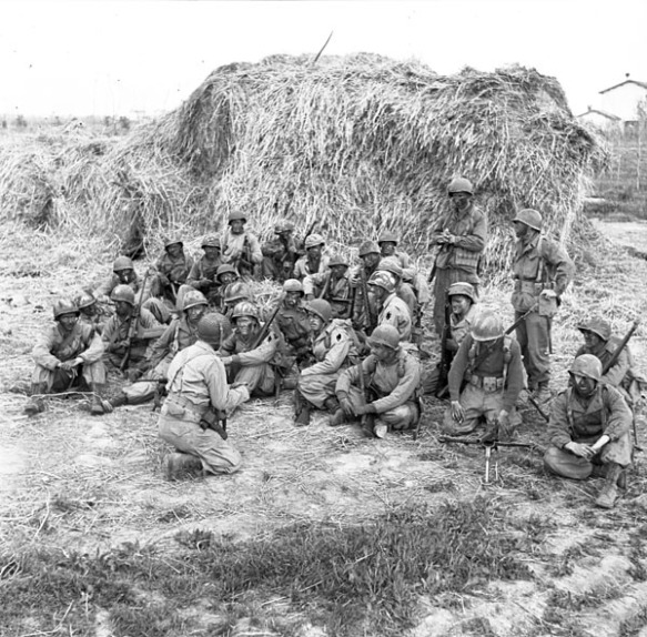 Photo noir et blanc d'environ vingt-cinq soldats, assis devant une énorme meule de foin, recevant des instructions avant d'effectuer une patrouille.