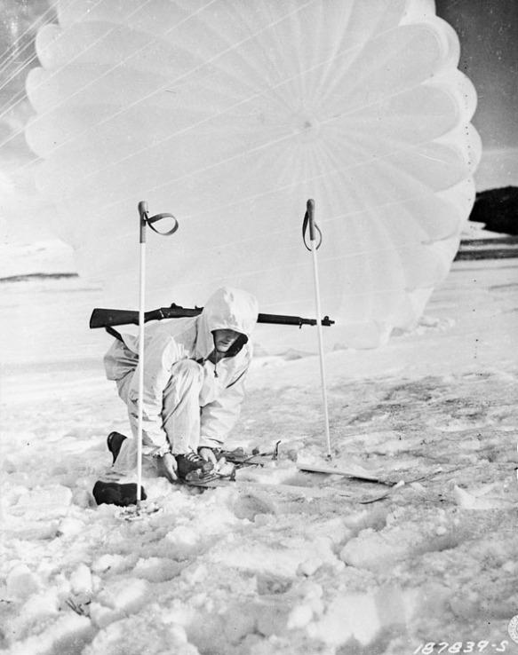 Photo noir et blanc d'un soldat portant une combinaison d'hiver blanche, accroupi pour ajuster ses fixations de ski. Un parachute est déployé derrière lui.