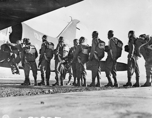 Photo noir et blanc d'une douzaine de soldats portant un équipement de parachutiste, faisant la queue pour monter à bord d'un Douglas C-47 pour un entraînement.