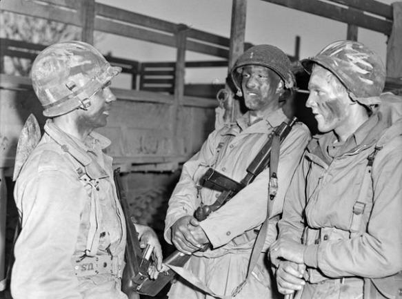 Photo noir et blanc de trois soldats, le visage enduit de cirage noir en guise de camouflage, se préparant à effectuer une patrouille de soirée.