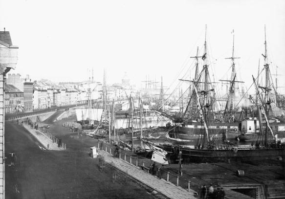 Une photographie en noir et blanc d'un port animé, où l'on voit une rue bordée d'édifices et un quai où sont amarrés nombre de bateaux.
