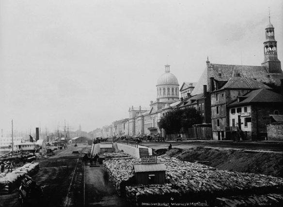 Une photographie en noir et blanc d'un quai sur lequel s'alignent diverses marchandises, ainsi que d'un grand édifice de style néoclassique et d'une église qui font face à la rive.