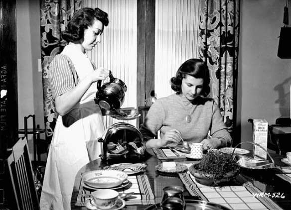 Photographie en noir et blanc d'une femme debout versant du café dans une tasse pour une autre femme assise à une table en train de déjeuner.