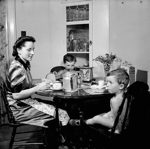 Photographie en noir et blanc d'une femme et de ses deux jeunes fils assis à une table en train de déjeuner.