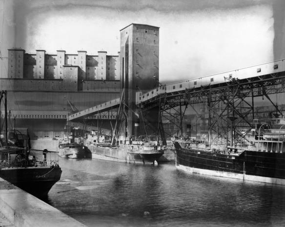 Photo noir et blanc de trois navires mis à quai. Un bâtiment administratif est situé à l'arrière-plan. Le long du quai se trouve une large structure de déchargement avec des treuils et des échafaudages.