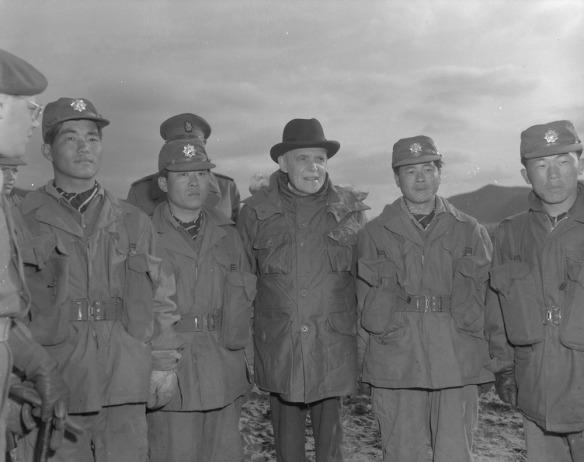 Photo noir et blanc de Louis St-Laurent entouré de militaires. Deux soldats sud-coréens se tiennent à sa gauche, et deux autres à sa droite. À l'arrière-plan, on distingue deux soldats canadiens. Au premier plan, à gauche, on aperçoit le profil partiel d'un soldat canadien portant des lunettes et un képi.