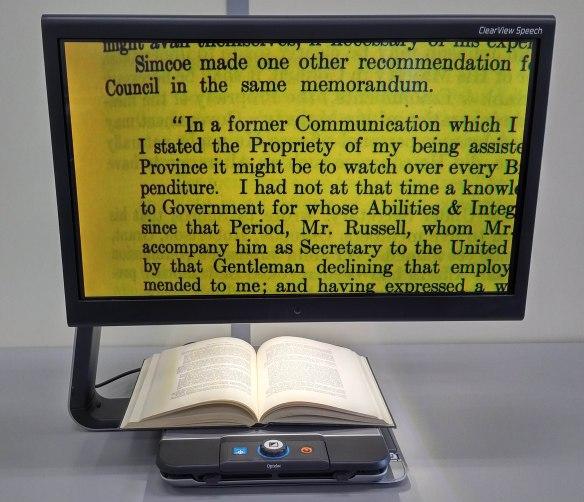 Photo couleur d'un appareil d'aide à la lecture comportant un plateau mobile doté de boutons de contrôle, sur lequel est déposé un livre. Le texte agrandi est affiché sur un écran en gros caractères noirs sur fond jaune.