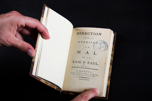 Photo couleur d'un livre ouvert à la page titre, où on peut lire « Direction pour la guerison du mal de la Baie St Paul. A Quebec : Chez Guillaume Brown, au milieu de la grande côte. M, DCC, LXXXV. »