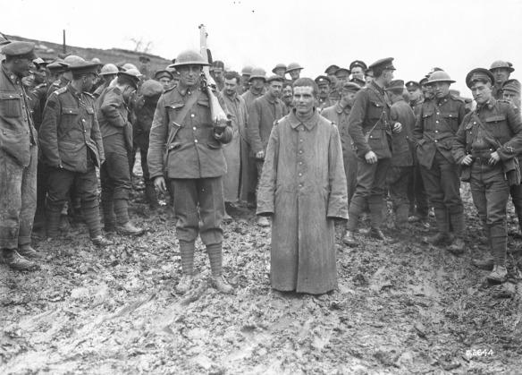 Photo noir et blanc d'un groupe de soldats entourant un combattant ennemi récemment capturé.