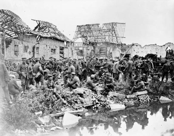 Photo noir et blanc montrant un large groupe de soldats allemands rassemblés entre un village et une rivière ou un canal. Les bâtiments à l'arrière-plan sont en bonne partie détruits.