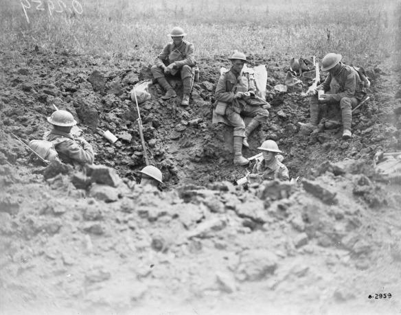 Photo noir et blanc de six soldats portant un casque, assis dans un large trou creusé dans la boue. Certains mangent, d'autres tiennent leur fusil faisant dos au photographe.