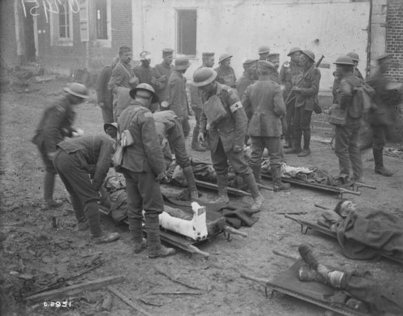 Photo noir et blanc de brancardiers et de personnel médical s'occupant de soldats blessés alors que d'autres soldats sont debout en arrière-plan.