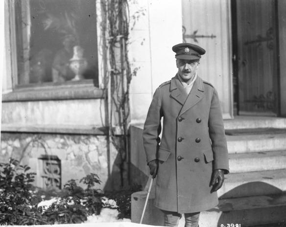 Photo noir et blanc d'un officier devant un bâtiment; il porte une casquette d'officier et tient un bâton de marche dans sa main droite.