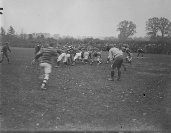 Photo noir et blanc de deux équipes de rugby en pleine mêlée. Deux arbitres surveillent la séquence de jeu.
