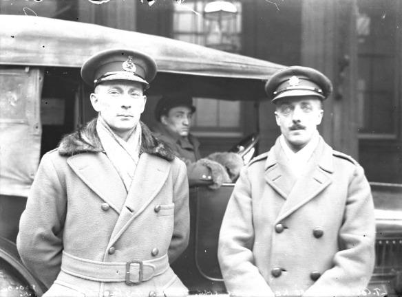 Photo noir et blanc de deux officiers devant une voiture dans laquelle le conducteur est assis. Ils portent tous deux une casquette d'officier et un pardessus.