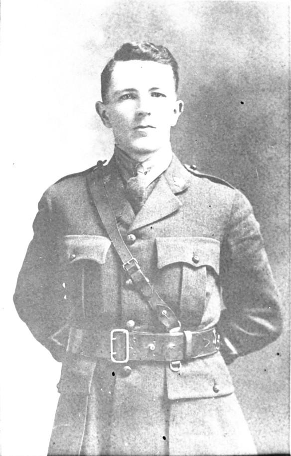 Photo noir et blanc d'un officier portant un ceinturon-baudrier, les mains derrière le dos.