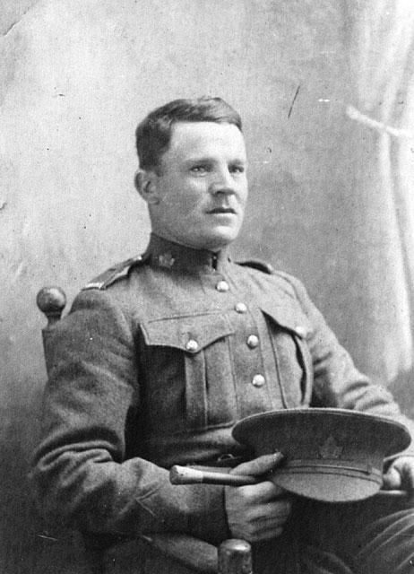 Photo noir et blanc d'un soldat assis tenant sa casquette et sa badine sur ses genoux.