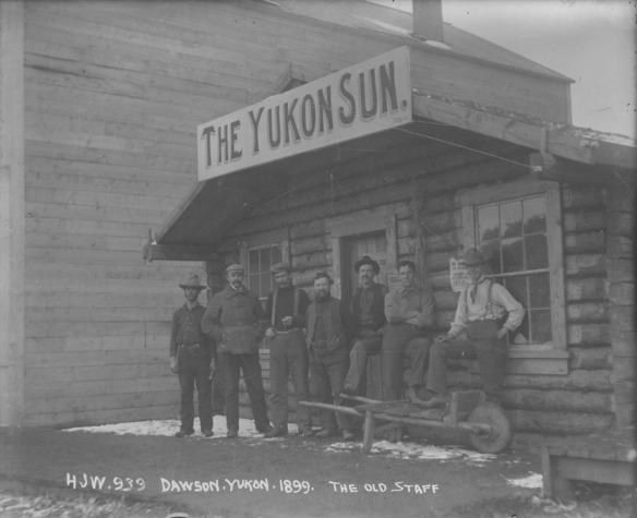 Photo noir et blanc d'un groupe d'hommes devant une cabane en bois rond dont l'enseigne indique « The Yukon Sun ».