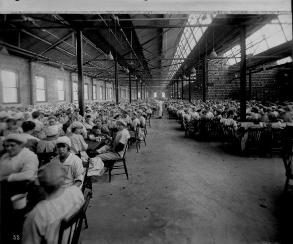 Photo noir et blanc d'une grande cafétéria dans une usine, où dînent des centaines de femmes en tenue d'ouvrière.