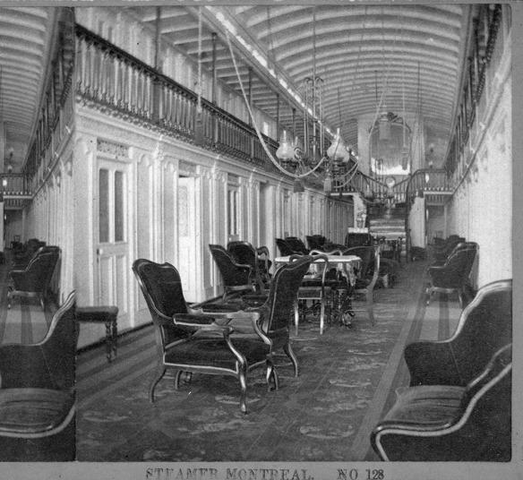 Photo noir et blanc de l'intérieur du navire à vapeur Montreal montrant une grande salle d'attente recouverte de tapis avec de nombreux fauteuils rembourrés