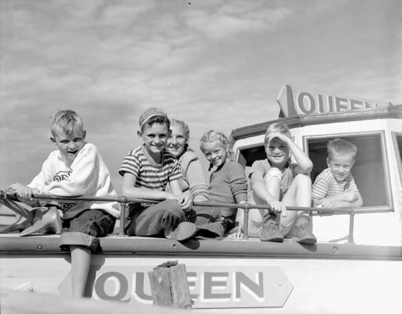Photo noir et blanc de deux fillettes et de quatre garçons assis sur le pont avant du bateau à moteur Queen