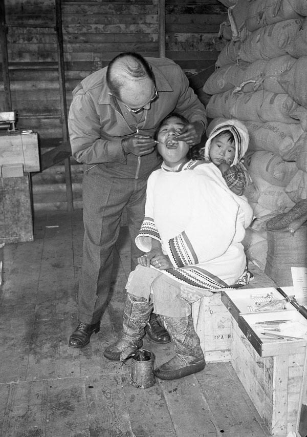 Photo noir et blanc d'une femme avec un enfant dans un amauti, se faisant examiner les dents par un dentiste.