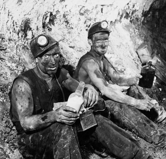 Photo noir et blanc de deux hommes prenant leur dîner dans un tunnel; ils sont couverts de poussière et portent une tenue de mineur.