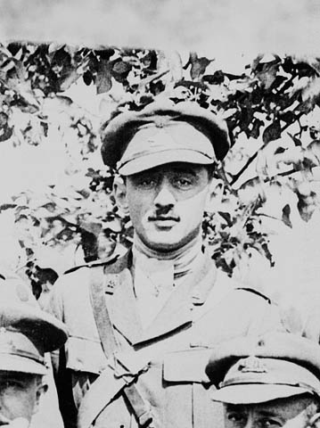 Photo noir et blanc d'un soldat en uniforme regardant directement vers l'appareil photo. Il se tient derrière deux autres hommes en uniforme dont les visages sont partiellement visibles au premier plan. On aperçoit un arbre en arrière-plan.