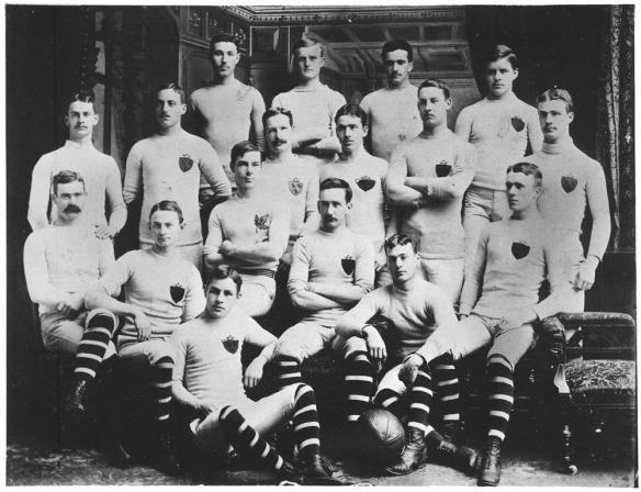 Photo noir et blanc de l'équipe de rugby de l'Université McGill lors de la saison 1884-1885. James Naismith est assis avec ses coéquipiers (2e rangée, premier à gauche).