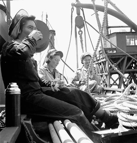 Photo noir et blanc de trois femmes prenant leur dîner dans une barque à côté de rames et d'une corde enroulée.