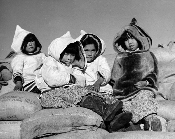 Photo noir et blanc de quatre enfants assis sur des sacs de farine.