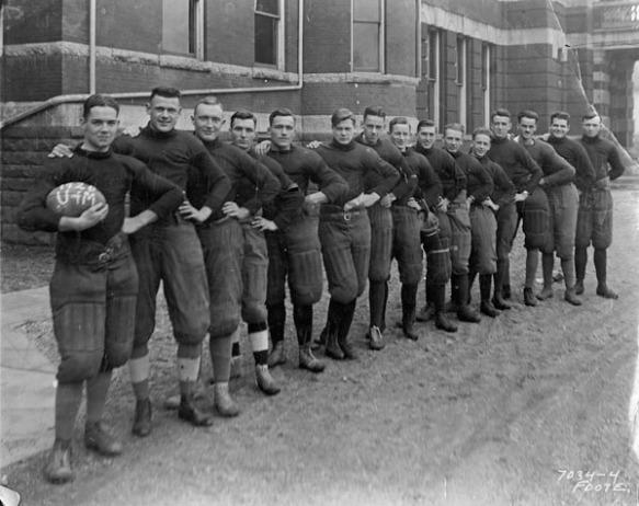 Photo noir et blanc d'une équipe senior de rugby universitaire, en Ontario. Les membres se tiennent en rangée, de biais, la main gauche sur la hanche et la main droite sur l'épaule de la personne devant.