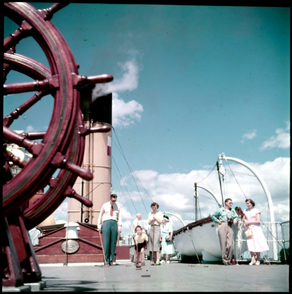 A colour photograph of a boy playing shuffleboard, watched by a man and a woman on the Canadian Pacific Railway cruise ship Assiniboia.Photo couleur d'un garçon jouant aux galets sur le navire de croisière Assiniboia du Canadien Pacifique; un homme et une femme l'observent.