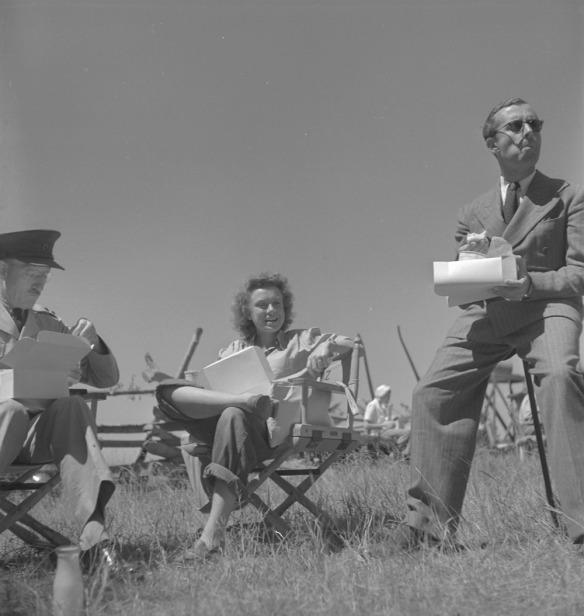 Photo noir et blanc de l'actrice Lucia Carroll et de deux membres de la distribution du film Les Chevaliers du ciel en train de dîner en plein air sur le lieu du tournage.