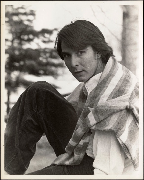 Texte alternatif : Photo en noir et blanc d'un jeune homme assis avec un chandail sur les épaules.