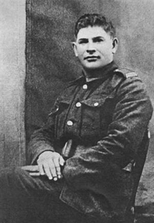 Photo noir et blanc d'un soldat en uniforme assis sur une chaise, les mains croisées, regardant vers l'appareil photo.
